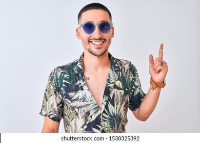 Young handsome man wearing Hawaiian sumer shirt and blue sunglasses over isolated background with a big smile on face, pointing with hand and finger to the side looking at the camera.