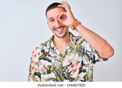 Young handsome man wearing Hawaiian summer shirt over isolated background doing ok gesture with hand smiling, eye looking through fingers with happy face.