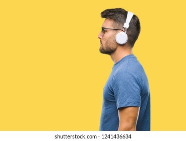 Young handsome man wearing headphones listening to music over isolated background looking to side, relax profile pose with natural face with confident smile.