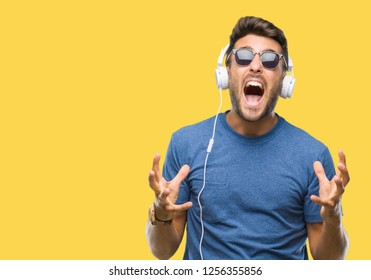 Young handsome man wearing headphones listening to music over isolated background crazy and mad shouting and yelling with aggressive expression and arms raised. Frustration concept.