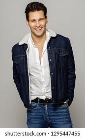 Young handsome man wearing jeans outfit and smiling isolated over gray background