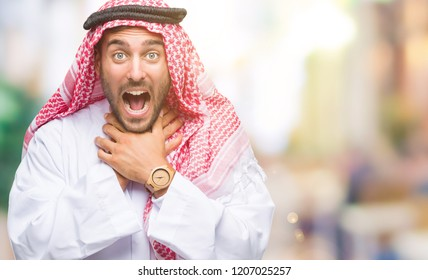 Young handsome man wearing keffiyeh over isolated background shouting and suffocate because painful strangle. Health problem. Asphyxiate and suicide concept.