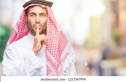 Young handsome man wearing keffiyeh over isolated background asking to be quiet with finger on lips. Silence and secret concept.