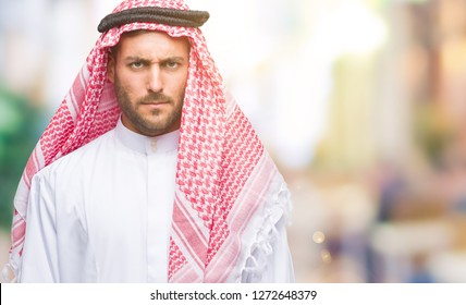 Young handsome man wearing keffiyeh over isolated background skeptic and nervous, frowning upset because of problem. Negative person.