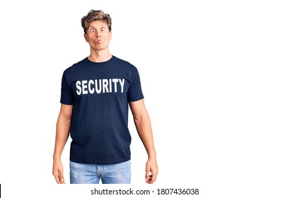 Young handsome man wearing security t shirt making fish face with lips, crazy and comical gesture. funny expression.
