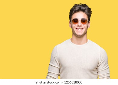 Young handsome man wearing sunglasses over isolated background with a happy and cool smile on face. Lucky person.