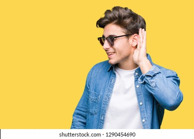 Young handsome man wearing sunglasses over isolated background smiling with hand over ear listening an hearing to rumor or gossip. Deafness concept.
