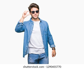 Young handsome man wearing sunglasses over isolated background smiling and confident gesturing with hand doing size sign with fingers while looking and the camera. Measure concept.