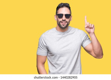 Young handsome man wearing sunglasses over isolated background surprised with an idea or question pointing finger with happy face, number one