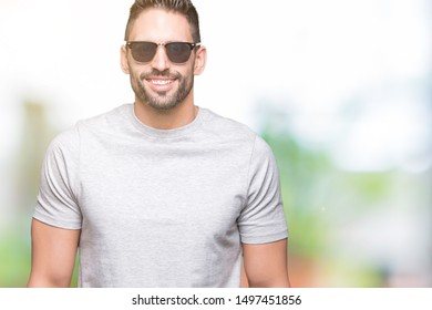 Young handsome man wearing sunglasses over isolated background with a happy face standing and smiling with a confident smile showing teeth