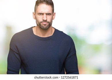 Young handsome man wearing sweater over isolated background skeptic and nervous, frowning upset because of problem. Negative person.