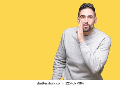 Young handsome man wearing sweatshirt over isolated background hand on mouth telling secret rumor, whispering malicious talk conversation