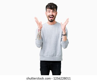 Young handsome man wearing sweatshirt over isolated background celebrating crazy and amazed for success with arms raised and open eyes screaming excited. Winner concept