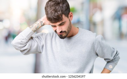 Young handsome man wearing sweatshirt over isolated background Suffering of neck ache injury, touching neck with hand, muscular pain