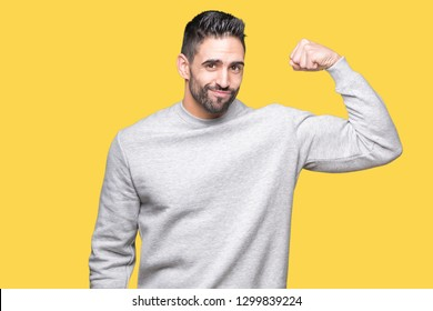 Young handsome man wearing sweatshirt over isolated background Strong person showing arm muscle, confident and proud of power