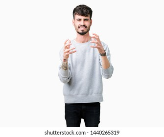 Young handsome man wearing sweatshirt over isolated background Shouting frustrated with rage, hands trying to strangle, yelling mad