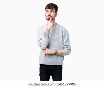 Young handsome man wearing sweatshirt over isolated background with hand on chin thinking about question, pensive expression. Smiling with thoughtful face. Doubt concept.