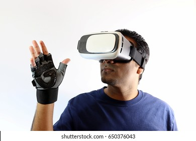 84fe160c5630 Young handsome man wearing virtual reality goggles waving high with remote  control gloves