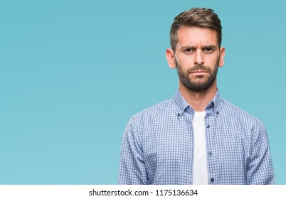 Young handsome man wearing white t-shirt over isolated background skeptic and nervous, frowning upset because of problem. Negative person.