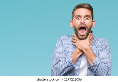 Young handsome man wearing white t-shirt over isolated background shouting and suffocate because painful strangle. Health problem. Asphyxiate and suicide concept.