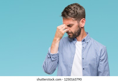 Young handsome man wearing white t-shirt over isolated background tired rubbing nose and eyes feeling fatigue and headache. Stress and frustration concept.
