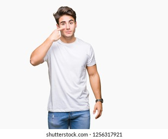 Young handsome man wearing white t-shirt over isolated background Pointing with hand finger to face and nose, smiling cheerful
