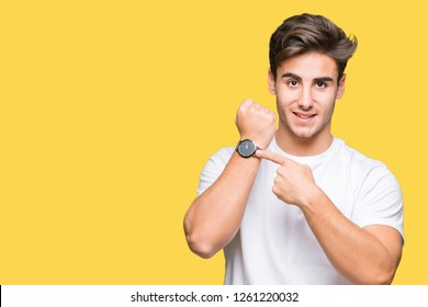 Young handsome man wearing white t-shirt over isolated background In hurry pointing to watch time, impatience, upset and angry for deadline delay