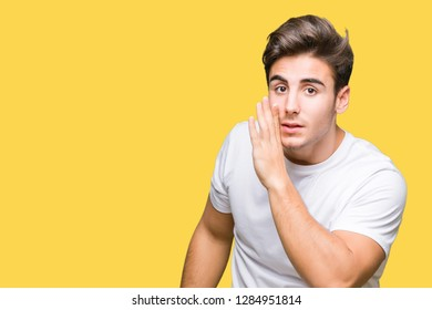 Young handsome man wearing white t-shirt over isolated background hand on mouth telling secret rumor, whispering malicious talk conversation