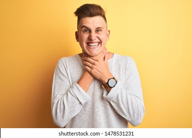Young handsome man wearing white casual t-shirt standing over isolated yellow background shouting and suffocate because painful strangle. Health problem. Asphyxiate and suicide concept.