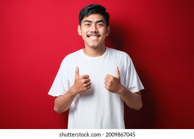 Young handsome man wearing white t-shirt over red background approving doing positive gesture with hand, thumbs up smiling and happy for success. Winner gesture.