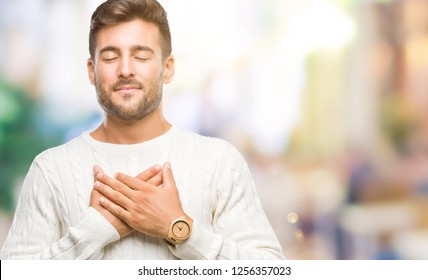 Young handsome man wearing winter sweater over isolated background smiling with hands on chest with closed eyes and grateful gesture on face. Health concept.