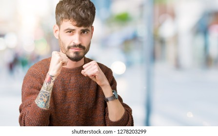Young handsome man wearing winter sweater over isolated background Ready to fight with fist defense gesture, angry and upset face, afraid of problem