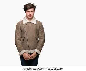 Young handsome man wearing winter coat over isolated background skeptic and nervous, frowning upset because of problem. Negative person.
