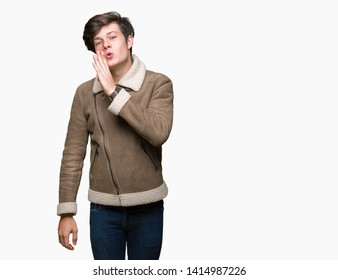 Young handsome man wearing winter coat over isolated background hand on mouth telling secret rumor, whispering malicious talk conversation