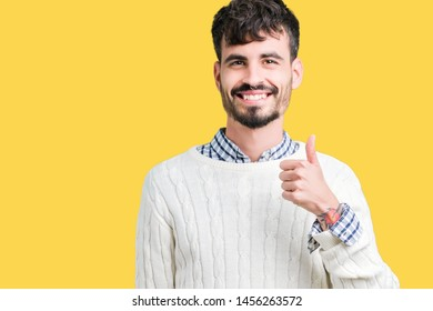 Young handsome man wearing winter sweater over isolated background doing happy thumbs up gesture with hand. Approving expression looking at the camera showing success.