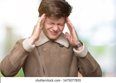Young handsome man wearing winter coat over isolated background suffering from headache desperate and stressed because pain and migraine. Hands on head.