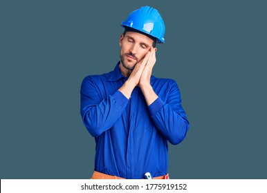 Young handsome man wearing worker uniform and hardhat sleeping tired dreaming and posing with hands together while smiling with closed eyes.