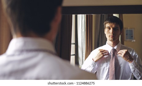 Young handsome man in white shirt stands by the mirror tying a tie