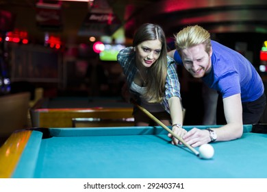 Young handsome man and woman flirting while playing billiard