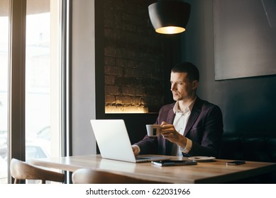 Young handsome man working in the office of mobile network company, adapting tariff plans to users need. Consultant providing service online with notebook. Business running through mobile systems.