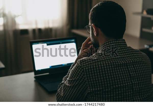 Young handsome man working on a laptop in glasses and a protective mask, reads the news online. Online business, work at home, lectures remotely. Quarantine, coronavirus, stay home, depression, crisis