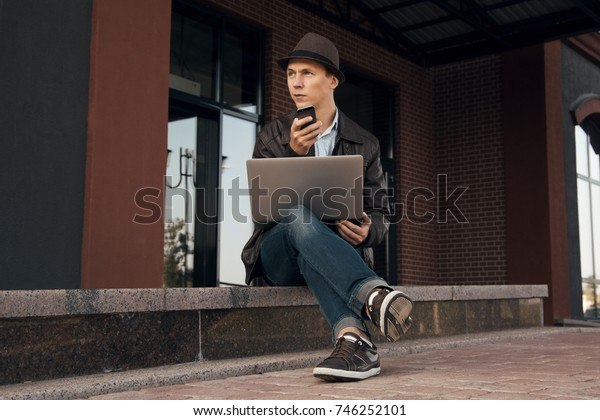 Young handsome man working on his break near office. Stylish guy sitting on stairs in the city center. Happy boy doing his job anywhere he can. Freelancer using his notebook and mobile phone outside.