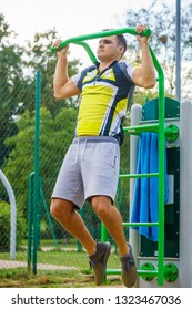 Young handsome man working out in outdoor gym. Sporty guy flexing his muscles doing pull ups on machine. Staying fit and healthy.