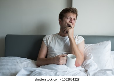 Young handsome man yawning and having morning coffee in bed. He is tired or have hangover after party