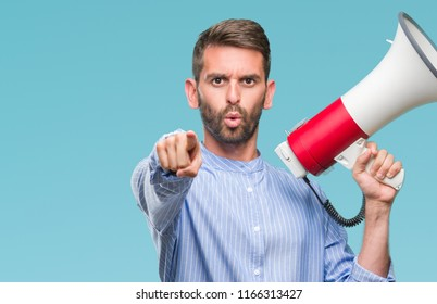 Young handsome man yelling through megaphone over isolated background pointing with finger to the camera and to you, hand sign, positive and confident gesture from the front