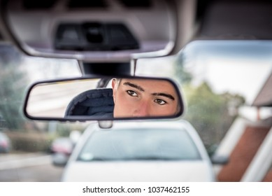 Young handsome man's reflection in the rearview mirror of car. Concept: beauty, fashion, transportation, travel