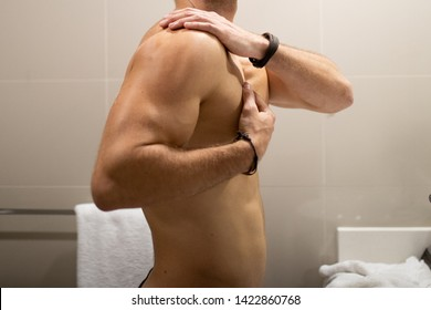 Young handsome masculine caucasian man looking at the mirror in the bathroom and put the lotion on his body. Routine health care for men. His hands touching his body and look at camera.