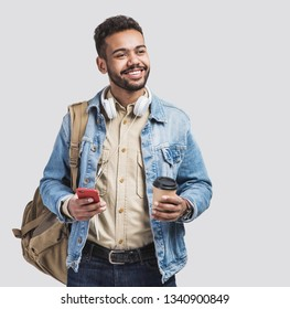 Young handsome men with backpack holding smart phone and coffee. Smiling student man going on a travel. Isolated on gray background