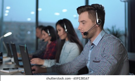 Young handsome men in checked shirt and headset working in call center in modern worldwide office he talking and looking on screen of desktop computer