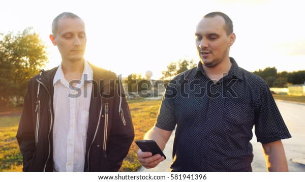 Young handsome men have a serious talk while walking in the city during beautiful sunset with lense flare effects
